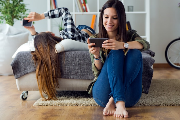 Dos hermosas mujeres jóvenes utilizando teléfono móvil en casa.
