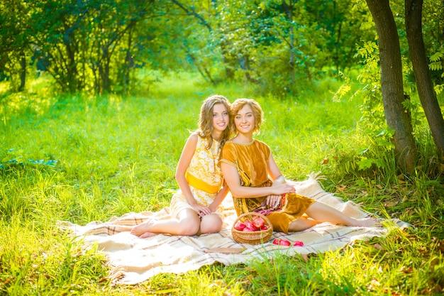 Dos hermosas mujeres jóvenes con vestidos amarillos y marrones con libro y canasta de manzanas en el picnic en el parque