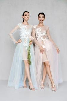 Dos hermosas mujeres jóvenes en vestidos de tul transparente con encaje posando de manera idéntica