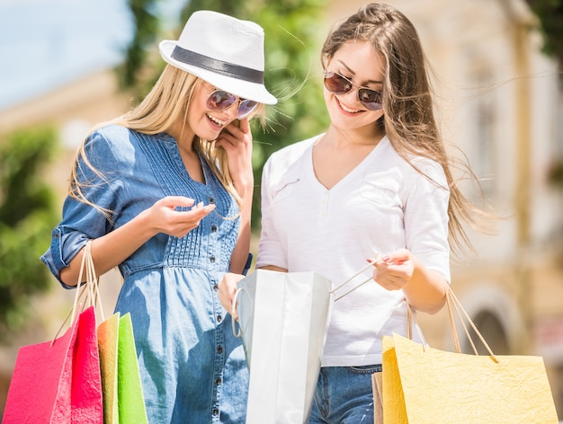 Dos hermosas mujeres mirando dentro de bolsas de compras en la ciudad.
