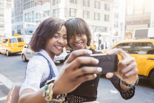 Dos hermosas mujeres negras tomando selfie en nueva york