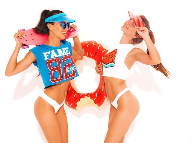 Dos hermosas mujeres sexy sonrientes en calzoncillos de verano blanco y tema. chicas con gafas de sol, visera transparente. modelos con colchón inflable donut lilo y patineta centavo. aislado