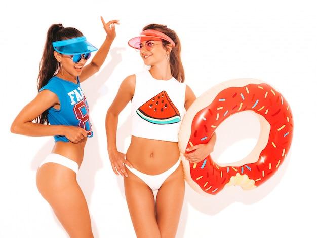 Dos hermosas mujeres sexy sonrientes en calzoncillos de verano blanco y tema. chicas con gafas de sol, visera transparente. modelos positivos divirtiéndose con el colchón inflable donut lilo. aislado
