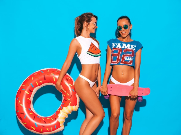 Dos hermosas mujeres sexy sonrientes en calzoncillos de verano y tema. chicas con gafas de sol. modelos positivos divirtiéndose con coloridas patinetas de centavo. con colchón inflable donut lilo