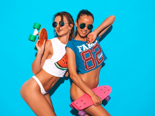 Dos hermosas mujeres sexy sonrientes en calzoncillos de verano y tema. chicas de moda en gafas de sol. modelos positivos divirtiéndose con coloridas patinetas de centavo. aislado
