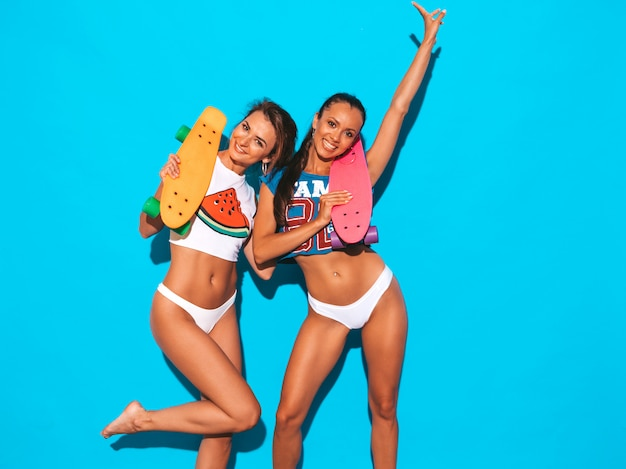 Dos hermosas mujeres sexy sonrientes en calzoncillos de verano y tema. chicas de moda modelos positivos divirtiéndose con coloridas patinetas de centavo. aislado. levantando la mano