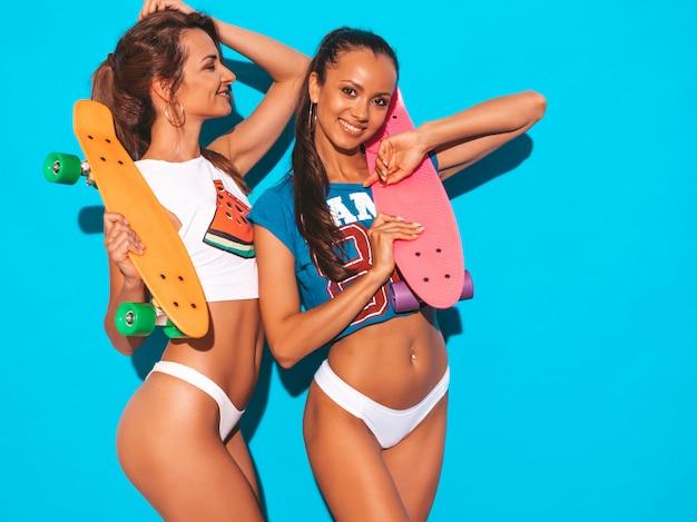 Dos hermosas mujeres sexy sonrientes en calzoncillos de verano y tema. chicas de moda modelos positivos divirtiéndose con coloridas patinetas de centavo. aislado