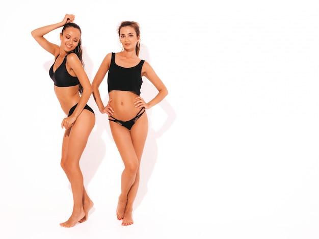 Dos hermosas mujeres sonrientes sexy en ropa interior negro. modelos calientes de moda divirtiéndose. chicas aisladas longitud total