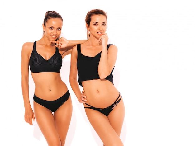 Dos hermosas mujeres sonrientes sexy en ropa interior negro. modelos calientes de moda divirtiéndose. chicas aisladas