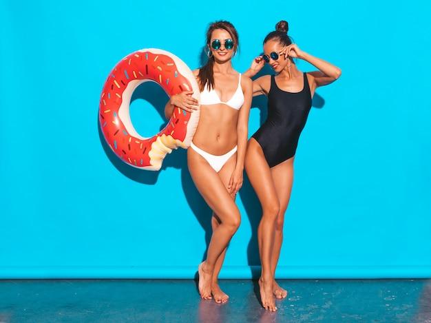 Dos hermosas mujeres sonrientes sexy en traje de baño blanco y negro de verano trajes de baño. chicas en gafas de sol. modelos positivos divirtiéndose con el colchón inflable donut lilo. aislado en la pared azul