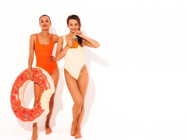 Dos hermosas mujeres sonrientes sexy en trajes de baño de verano coloridos trajes de baño. chicas aisladas modelos divertidos bebiendo cóctel fresco bebida lisa con colchón inflable donut lilo