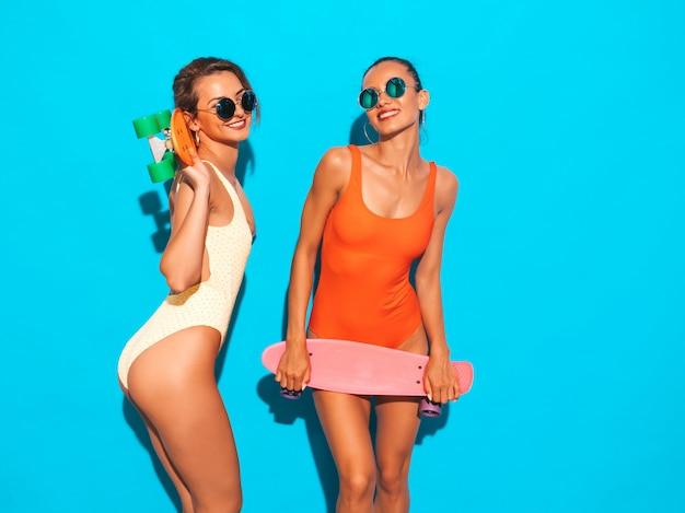 Dos hermosas mujeres sonrientes sexy en trajes de baño de verano coloridos trajes de baño. chicas de moda en gafas de sol. modelos positivos divirtiéndose con coloridas patinetas de centavo. aislado