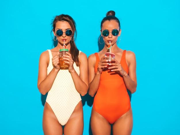 Dos hermosas mujeres sonrientes sexy en trajes de baño de verano coloridos trajes de baño. chicas de moda con gafas de sol. volviéndose loco. modelos divertidos aislados. beber un cóctel fresco bebida suave