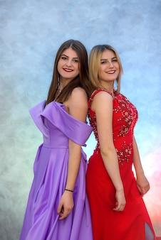Dos hermosas mujeres en vestidos elegantes celebrando el año nuevo
