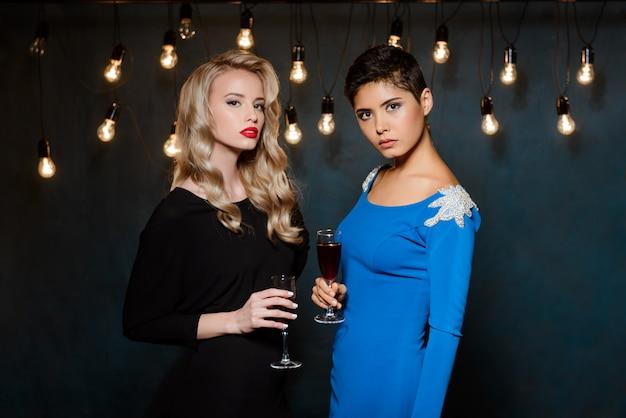 Dos hermosas mujeres en vestidos de noche posando, sosteniendo copas de vino