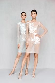 Dos hermosas mujeres con vestidos transparentes pálidos con detalles de encaje posando de manera idéntica