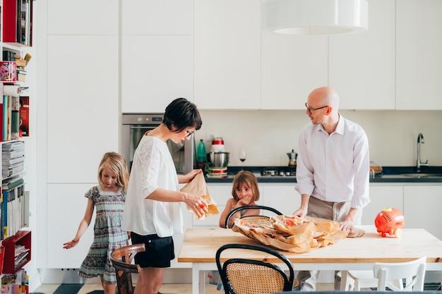 Dos hermosas niñas ayudando a sus padres a desempacar comestibles