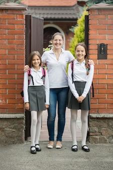 Dos hermosas niñas de pie con su madre en la puerta antes de ir a la escuela
