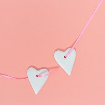 Dos hermoso corazón blanco colgando de una cinta rosa sobre fondo de papel de color rosa pastel. composición del día de san valentín o tarjeta de felicitación con espacio de copia para prueba o felicitaciones. estilo minimalista.