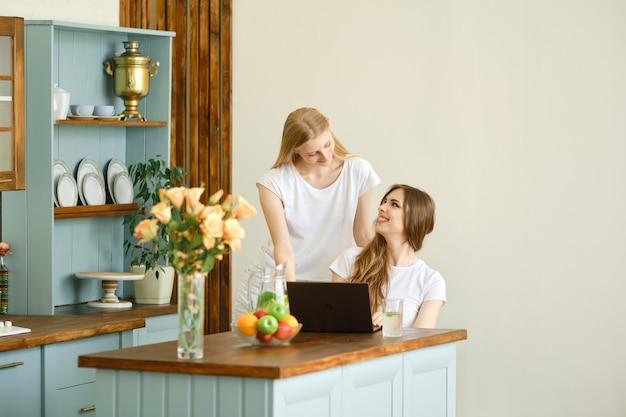Dos hermosos estudiantes haciendo videoconferencia sentados en la cocina