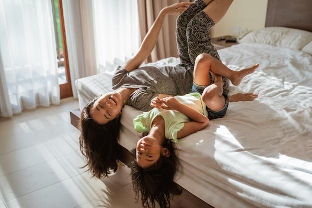 Dos hijita acostada en la cama con su madre a su lado