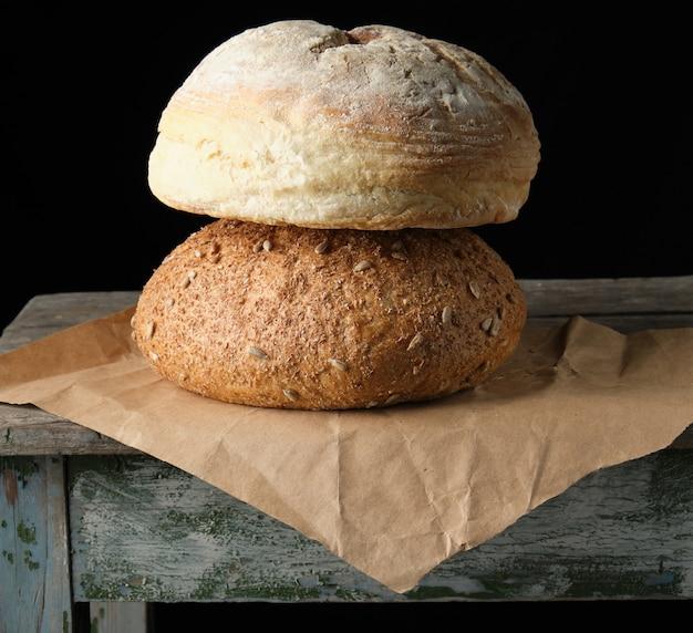 Dos hogazas de pan redondo horneado yacían sobre papel marrón