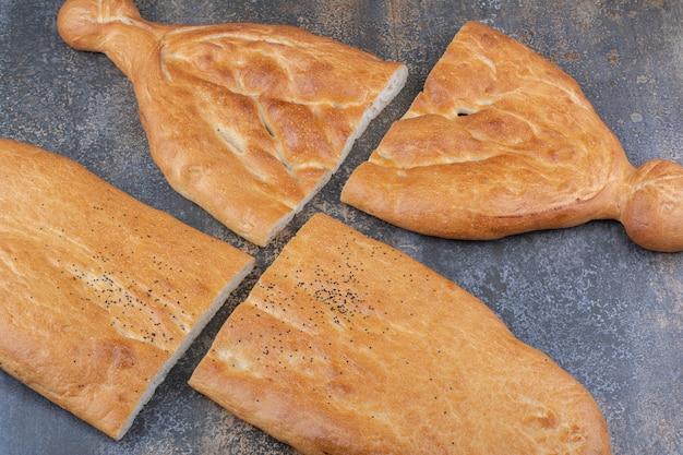 Dos hogazas de pan tandoori en mitades sobre la superficie de mármol