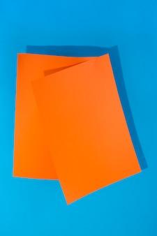 Dos hojas de papel naranja sobre un fondo azul para decoración, para diseño de texto, para una plantilla