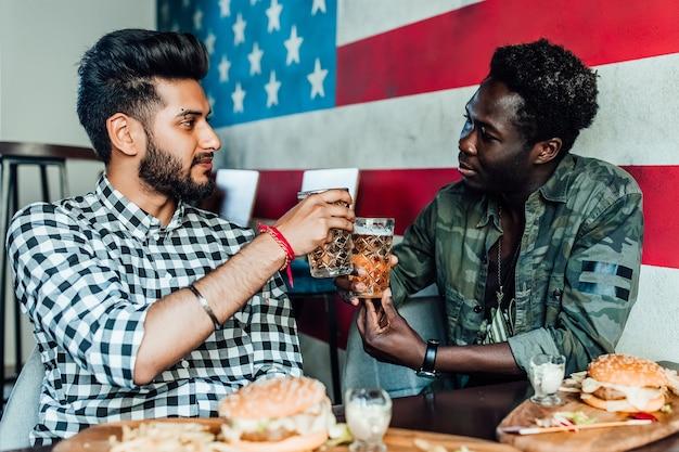 Dos hombre alegre divirtiéndose mientras pasa tiempo con amigos en un pub y bebiendo cerveza.