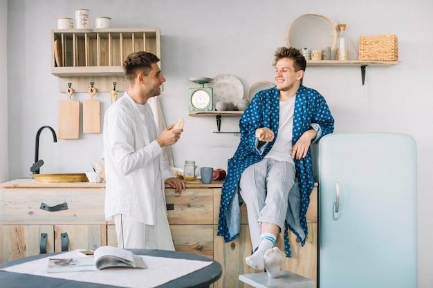 Dos hombre feliz desayunando por la mañana en la cocina