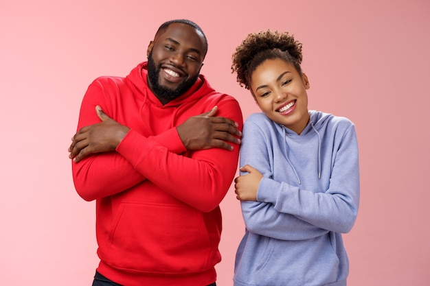 Dos hombre mujer afroamericana pareja se sienten cómodos juntos abrazándose abrazándose felizmente inclinando la cabeza mirada linda expresan amor fuerte relación sana, sonriendo encantado