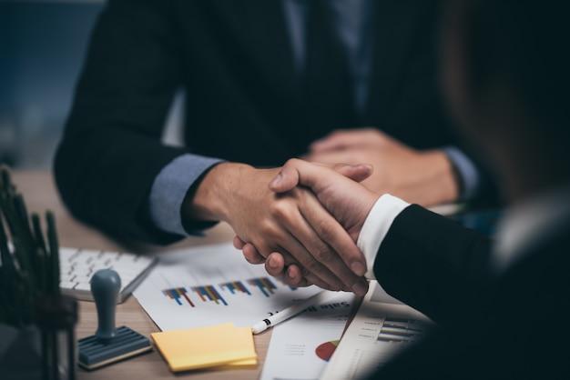Dos hombre de negocios confía en estrecharme la mano durante una reunión en la oficina, el éxito, el trato, el saludo y el concepto de socio.