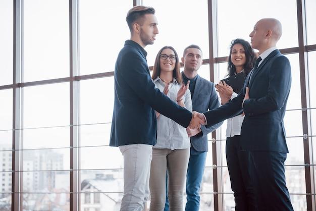 Dos hombre de negocios confía en estrecharme la mano durante una reunión en la oficina, saludo y concepto de socio