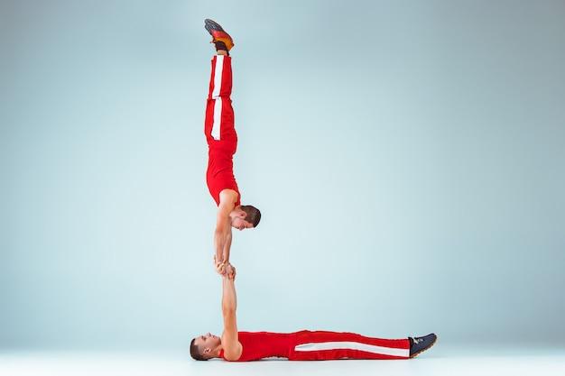 Los dos hombres acrobáticos en equilibrio posan