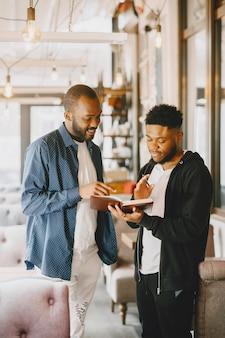 Dos hombres afroamericanos conversando. amigo sentado en un café.
