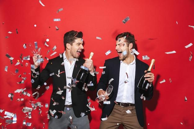 Dos hombres alegres elegantemente vestidos que se encuentran aisladas sobre el espacio rojo, celebrando el año nuevo