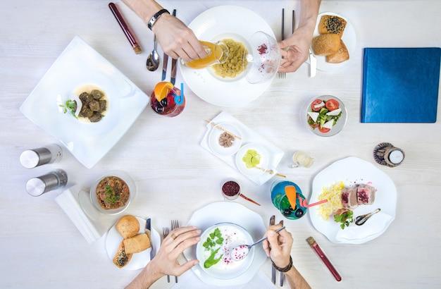 Dos hombres almorzando con dushbara, dovga, dolma, arroz y pollo envuelto