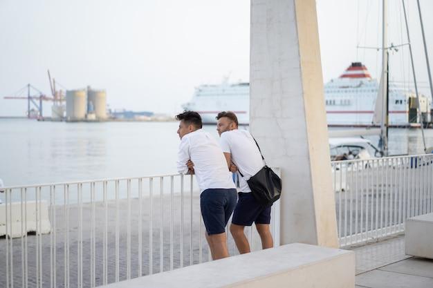 Dos hombres de un amigo en el paseo marítimo de la ciudad de málaga.