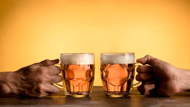 Dos hombres aplaudiendo con vasos de cerveza.