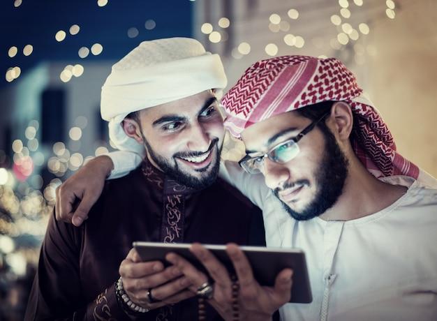 Dos hombres árabes con tableta en la ciudad de noche