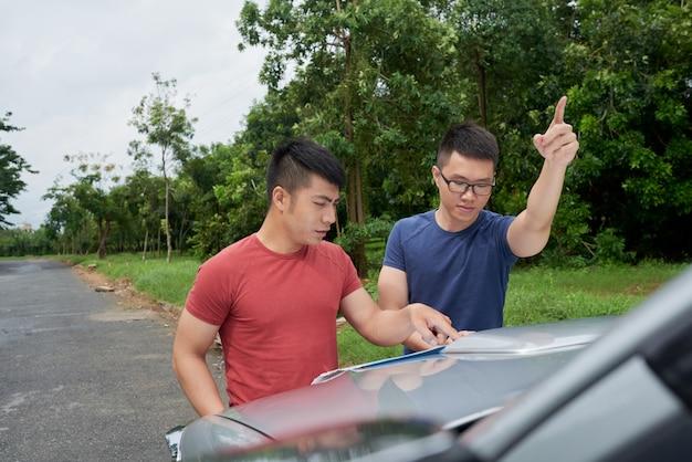 Dos hombres asiáticos de pie en coche en carretera, mirando el mapa y apuntando hacia adelante