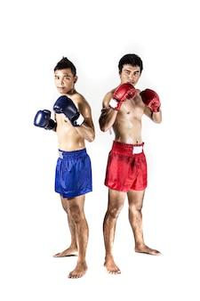 Dos hombres asiáticos que ejercen el boxeo tailandés en estudio de la silueta en el fondo blanco
