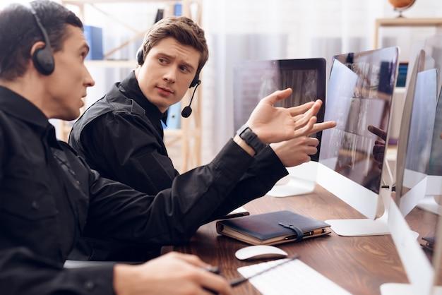 Dos hombres con auriculares están sobre sus cabezas.