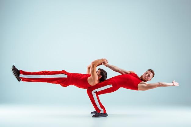 Los dos hombres caucásicos acrobáticos gimnásticos en pose de equilibrio