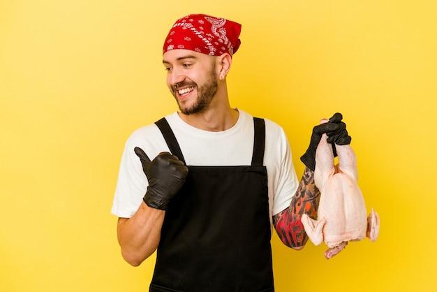 Dos hombres caucásicos tatuados jóvenes sosteniendo un pollo aislado en puntos de fondo amarillo con el dedo pulgar lejos, riendo y despreocupado.