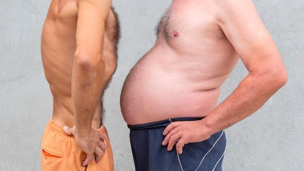 Dos hombres desnudos comparando barriga, hombre gordo de silueta grande y culturista delgado