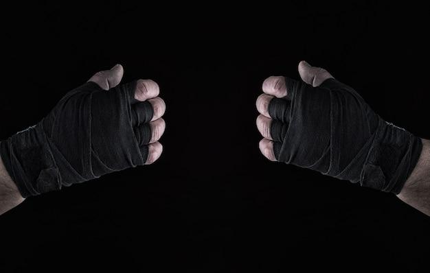 Dos hombres envueltos a mano en un vendaje deportivo negro.