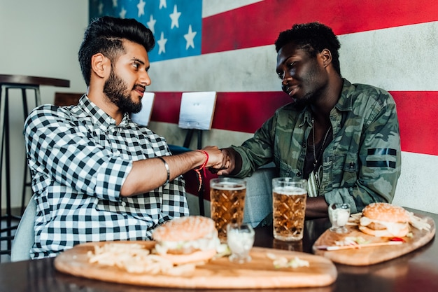 Dos hombres están sentados juntos en un salón de bar o restaurante darse las manos el uno al otro