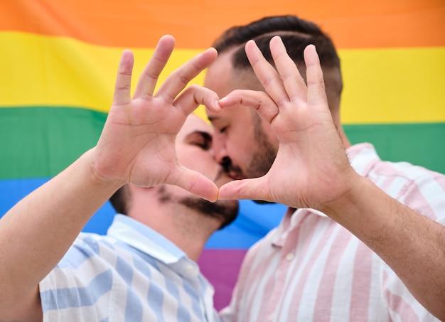 Dos hombres gays besándose detrás de una bandera del arco iris formando un corazón con sus manos