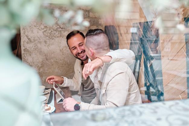 Dos hombres gays sonrientes usando una tableta en un restaurante